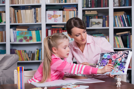 Child psychologist working with little girl's pictures