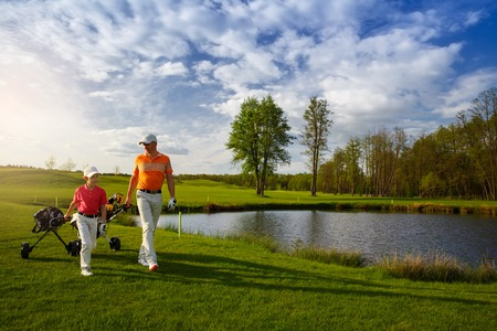 Photo for Father with son are walking at golf field - Royalty Free Image