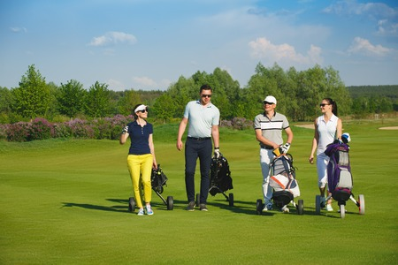 Four friends golfers walking on golf course at sunny day