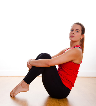 Young Woman sitting on the floor exercising in a studio