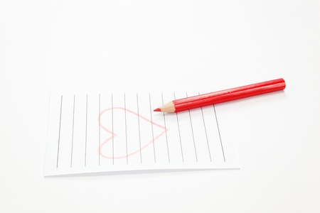 Heart drawn in red pencil on a white sheet of paper.