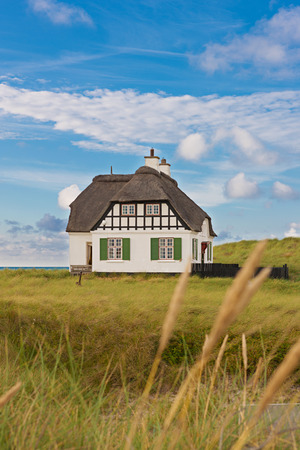 Thatched cottage right on the sea in summer