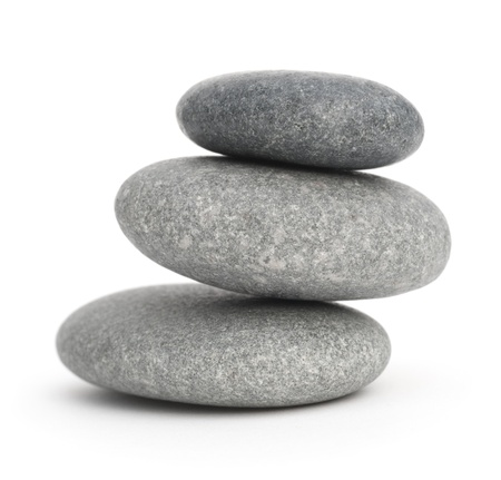 three pebbles stacked one onto each other, 3 stones over white background