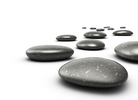 many pebbles on a white floor, stones are black with grey dots, there is a blur effecton the background, the front stone is clear