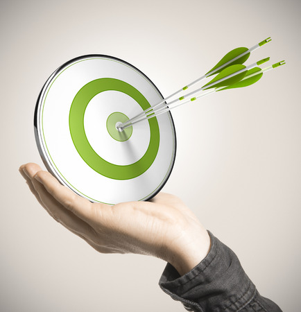 Photo pour Hand holding a green target with three arrows hitting the center over beige background  Business performance concept  - image libre de droit