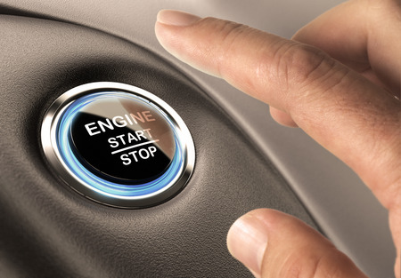 Foto de Car engine start and stop button with blue light and black textured background, close up and one finger - Imagen libre de derechos