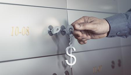 Photo pour Safe deposit in a bank vault, hand about to turn a key to open a safe box. Financial concept - image libre de droit
