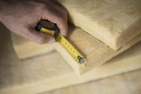 Hand measuring a fiberglass batt. Image of home insulation.