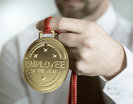 Photo pour Employee holding golden medal with the text employee of the year. Incentive or motivation concept - image libre de droit