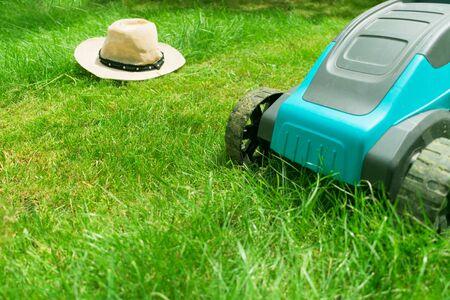 Foto de Lawn mower mowing green grass and a sunhat. Summer work in the garden. - Imagen libre de derechos