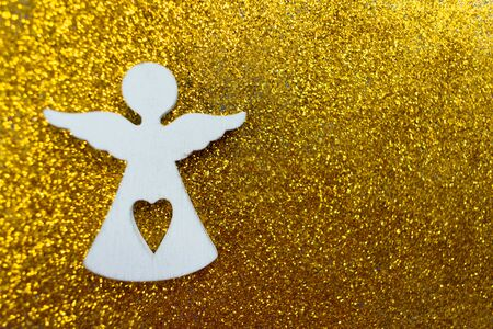 Photo pour Wooden figurine of a little white angel on a shiny golden background. Copy space. Christmas holiday concept. - image libre de droit