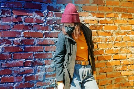Photo pour A sad girl in outerwear and a hat stands behind a brick wall in a black mask from the coronavirus - image libre de droit