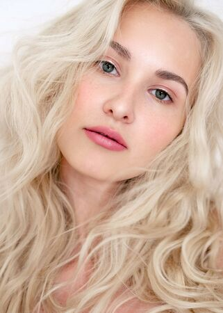 Photo for Portrait of a beautiful blonde model with lokans with natural makeup. Fashionable shiny marker on the skin, sexy lip gloss, makeu - Royalty Free Image
