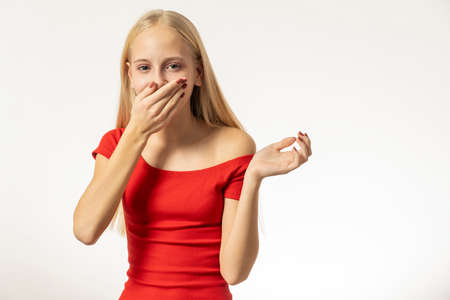 Photo pour Teenage girl with blond hair and in a red dress sneezes. high quality - image libre de droit