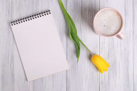Photo for Top view of a mockup of a blank notepad, a cup of coffee or cocoa and a yellow tulip on a light painted wooden surface. Selective focus. Copy space. - Royalty Free Image