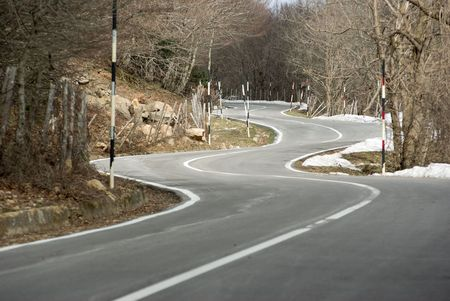 Road winding mountain crosses the wood