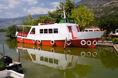 small, old, white and red ferryboat mooring on lake of Ioannina, Greece