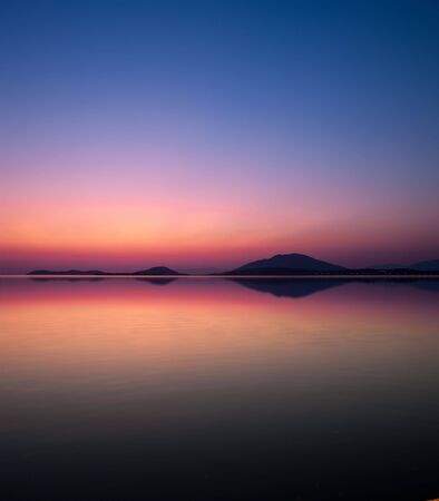 reflection of coastline in the sea of the harbor of Igoumenitsa (Greece) at twilight