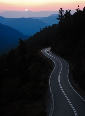 car travelling winding road between mountain at sunset
