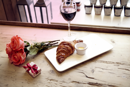 Romantic breakfast, Valentine's Day celebrating. Present box, rose flowers, fresh croissant, wine on wooden table. Focus on flowers. Daylight from window.