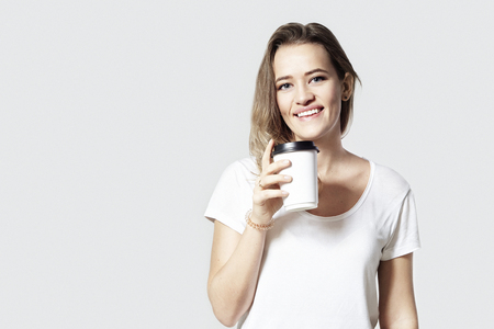 Pretty smiling young woman blonde hair with disposal paper cup of coffee, white background isolated.