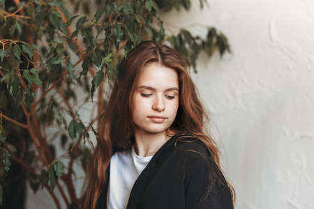 Photo for Portrait of a beautiful brooding young girl with long hair in an apartment with plants - Royalty Free Image