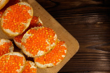 Sandwiches with butter and red caviar on wooden table