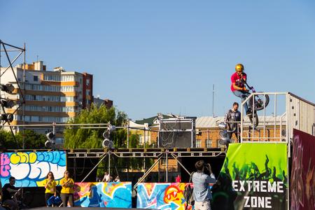 Kremenchug, Ukraine - June 5, 2017:  Extreme BMX rider in helmet in skatepark on competition. Unidentified BMX rider making tricks on festival Extreme zone