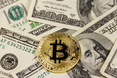 Golden bitcoin on hundred dollar bills background