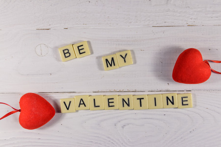 Foto de Red hearts and Be my Valentine text on white wooden background. Top view - Imagen libre de derechos