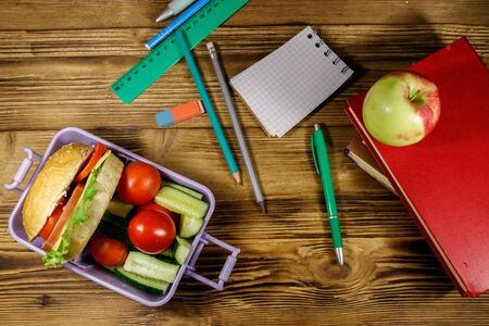 Photo for Back to school concept. School supplies, books, apple and lunch box with burgers and fresh vegetables on a wooden table. Top view - Royalty Free Image