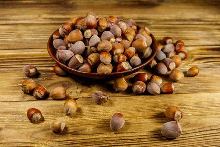 Foto für Hazelnuts in ceramic plate on a wooden table - Lizenzfreies Bild
