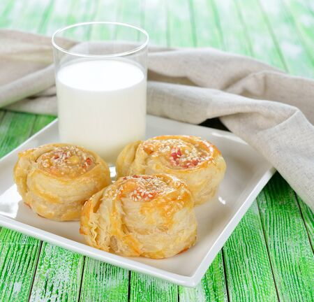 Puff pastry rolls with cheese on a white plate