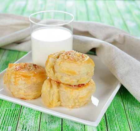 Puff pastry rolls with cheese and milk on a white plate