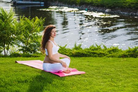 Photo pour Woman sits in lotus position. - image libre de droit