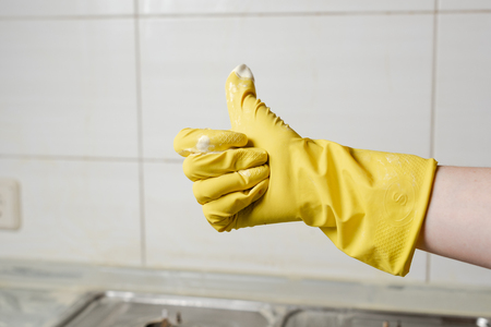 Photo pour Female hand in yellow glove showing thumb up - image libre de droit