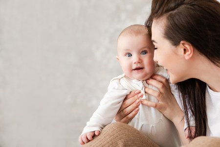 Photo for Charming infant girl in mother arms indoors - Royalty Free Image
