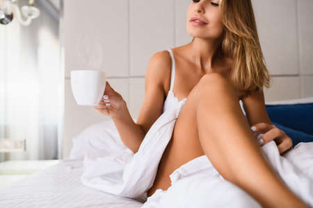 Photo pour Focus on heat from white cup of coffee, tea in hand of sexy lady in bedroom under white blanket indoors, beautiful breakfast in bed of luxury home, hotel. - image libre de droit