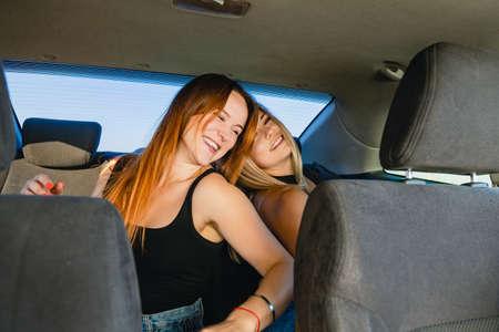 Photo pour Smiling female friends having fun, singing and dancing inside auto salon during road trip, crazy friendship and adventures. - image libre de droit