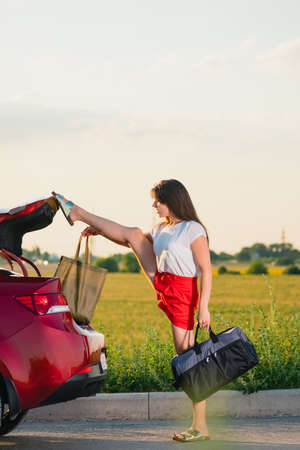 Foto de Young brunette girl in red shorts take bags and luggage out of vehicle trunk and touch door to close by leg - Imagen libre de derechos