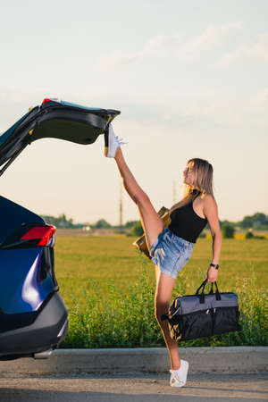 Foto de Sexy young woman raise leg up to close vehicle back after she took luggage bags during road trip - Imagen libre de derechos
