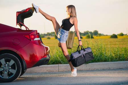 Foto de Sexy young woman raise leg up to close vehicle back after she took luggage bags. - Imagen libre de derechos