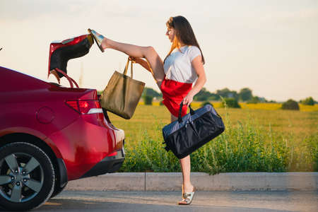 Foto de Young brunette woman in red shorts take bags and luggage out of vehicle trunk and touch door to close by leg - Imagen libre de derechos