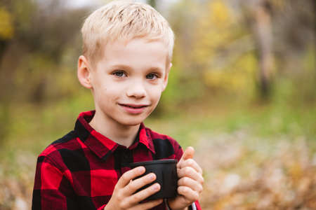Photo for Preteen blonde male child in red shirt holds black bottle cup with hot beverage. Happy family weekend at autumn park. - Royalty Free Image