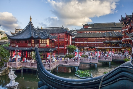 SHANGHAI - JULY 19: Yu garden on July 19, 2010 in Shanghai, China. View on Huxingting tea house on the back of  traditional chinese buildings and zigzag bridge crowded with people in Yu garden in Old Town of Shanghai