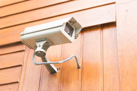 security camera and urban video on wooden wall