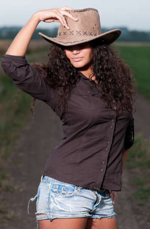 Beautiful cowboy woman with perfect hair and skin posing in country field