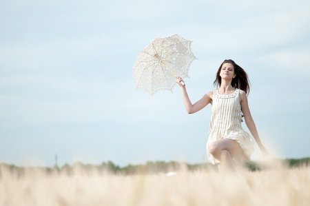 Beautiful sad and lonely woman with umbrella run in wheat field. Timed.