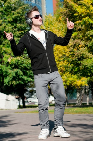 young casual cheerful man dancing outdoor in city park