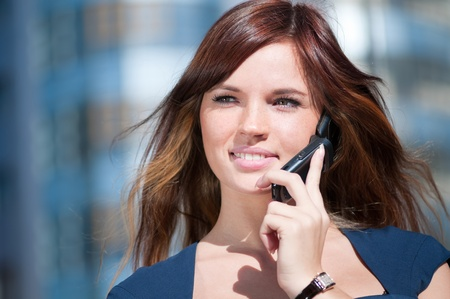 Young business woman using mobile cell phone over city background. Student